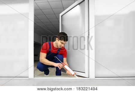 Young worker sealing joints of window in office