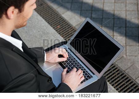 Close up of blank screen of laptop in hands of businessman