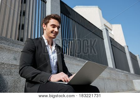 Smiling businessman working with laptop sitting on stairs