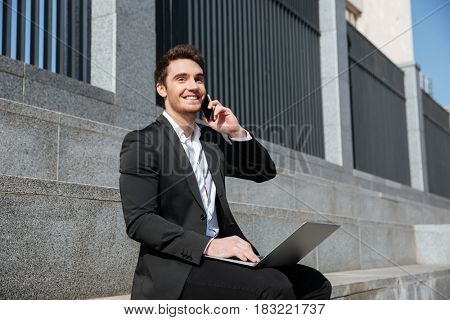 Cheerful man sitting with phone and laptop