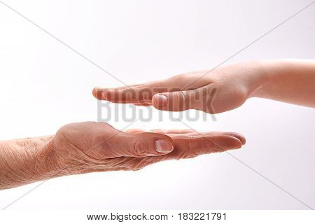 Unity of ages. Close up of wrinkled and smooth female hands. Isolated