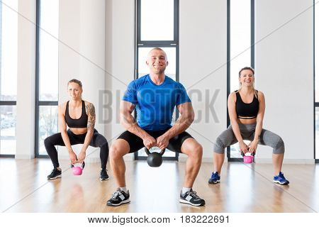 Crossfit group workout with kettlebells at the sports studio. Fitness and healthy lifestyle concept.