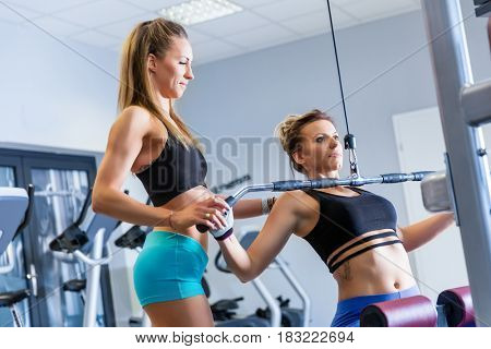 Personal trainer assists client while bodybuilding training at the gym. Professional help during workout. Healthy lifestyle and sport concept.