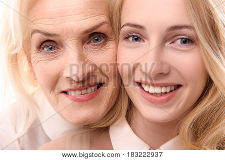 Joyful different aged women are looking at camera with happiness in their eyes. Portrait