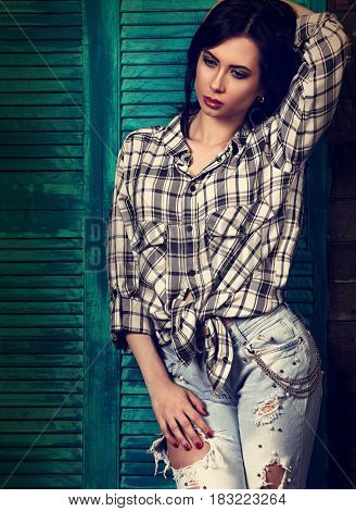 Beautiful Makeup Woman In Trendy Black And White Checkered Shirt And Blue Ripped Jeans Thinking And