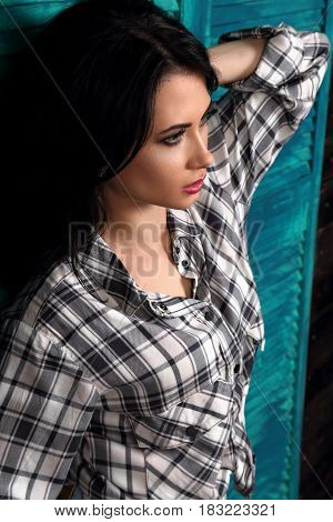 Beautiful Makeup Woman Profile In Trendy Black And White Checkered Shirt Thinking On Blue Wooden Bac