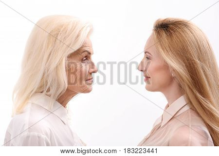 Smiling mother and daughter are looking at each other with love. Isolated