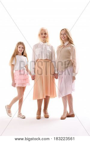 Happy grandmother is standing between her daughter and grandchild. They are holding hands, looking at camera with smile. Portrait. Isolated
