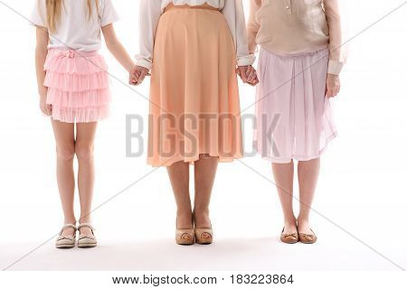 Grandmother, daughter and grandchild are holding hands. Isolated. Close up of legs