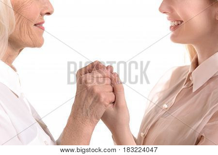 Generation connection. Mature woman is holding hands of her adult daughter. They are smiling. Close up. Isolated