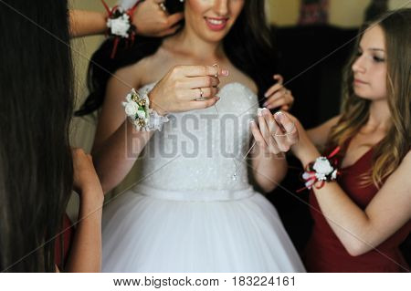 Happy Cheerful Brunette Bride Wearing At Her Room With Two Bridesmaids On Red Dress.