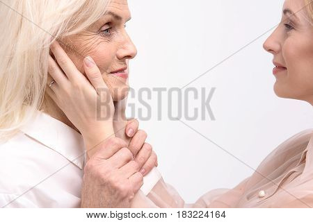 Smiling daughter is putting hands on face of her old mother. They are looking at each other with smile. Isolated