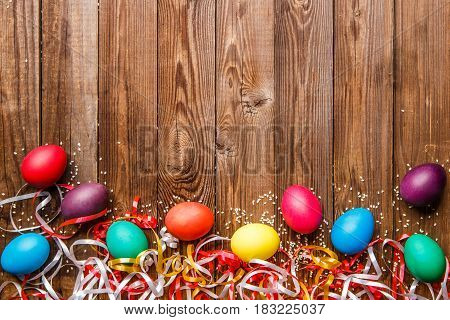 Festive eggs on empty wooden background with place for inscription