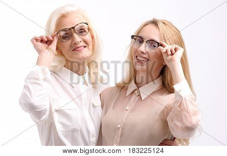 Happy smiling women are wearing eyewear and looking at camera. Isolated. Portrait