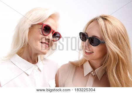 Happy smiling mother and daughter in sunny spectacles are standing together. Isolated