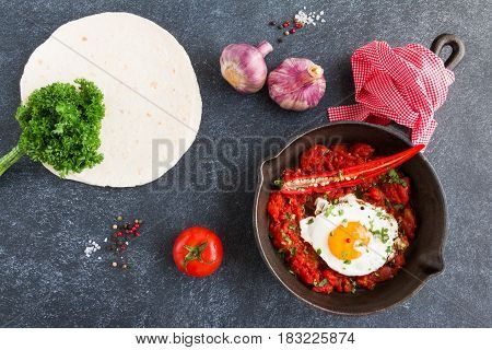 Huevos Rancheros traditional mexican dish fried eggs and salsa on a black cast-iron skillet on dark concrete background top view.