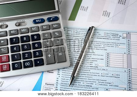Calculator with documents on table. Tax concept