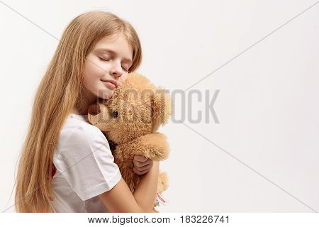 Little girl is hugging toylike bear and standing with closed eyes. Portrait. Isolated. Copy space on right side