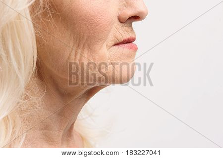 Wrinkles at face and neck of woman. Close up. Isolated. Copy space on right side