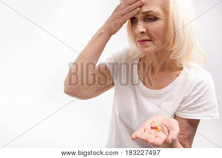 Mature lady is suffering from headache and holding pills. Isolated. Portrait. Copy space on left side