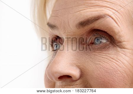 Close up of Bright eyes at mature female face. She is looking aside with interest. Isolated