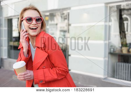 Portrait of excited young woman enjoying communication on smartphone. She is standing outdoors and holding cup of coffee. Lady is laughing. Copy space