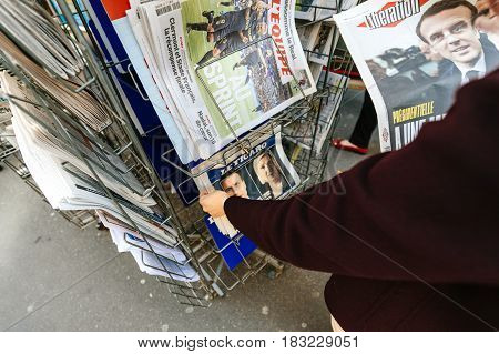 PARIS FRANCE - APRIL 24: Woman buy looks at press kiosk at French newspaper Le Figaro with pictures of French Presidential election candidates Emmanuel Macron Marine Le Pen a day after first round of French Presidential election on April 23 2017