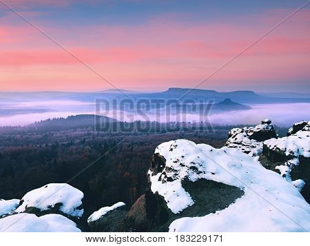 Red daybreak. Misty sunrise in the mountains the gradation of color clouds. Misty daybreak in a beautiful hills. Peaks of hills are sticking out from foggy background the fog is red and orange