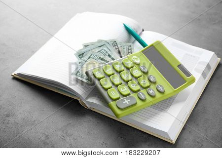 Calculator with money and notebook on gray background. Tax concept