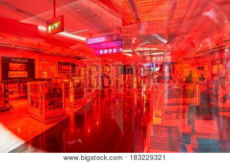 DUBAI, UAE - CIRCA JANUARY, 2017: view of Dubai International Airport Duty Free zone through red material. The airport is home to the long-haul carrier Emirates.