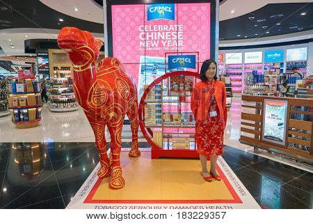 DUBAI, UAE - CIRCA JANUARY, 2017: promouter in red asian style clothing at Dubai International Airport. The airport is home to the long-haul carrier Emirates.