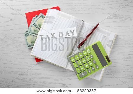 Calculator with money and notebook on wooden background. Tax concept