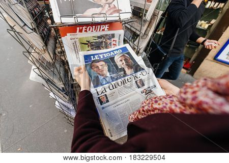 PARIS FRANCE - APRIL 24: Point of view Woman buy looks at press kiosk at French newspaper Le Figaro with pictures of French Presidential election candidates Emmanuel Macron Marine Le Pen a day after first round of French Presidential election on April 23