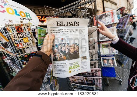PARIS FRANCE - APRIL 24: Man point of view persoanl perspective buy looks at press kiosk at Spanish newspaper El Pais with pictures of French Presidential election candidates Emmanuel Macron Marine Le Pen a day after first round of French Presidential ele