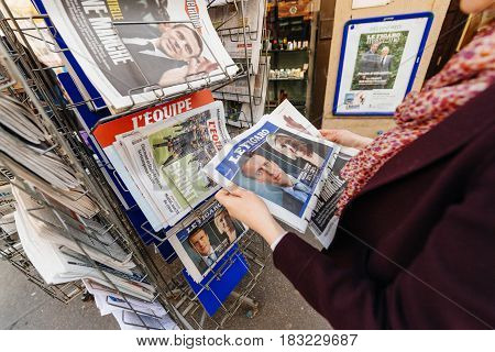 PARIS FRANCE - APRIL 24: Woman looks at press kiosk at French newspaper Le Figaro with pictures of French Presidential election candidates Emmanuel Macron Marine Le Pen a day after first round of French Presidential election on April 23 2017