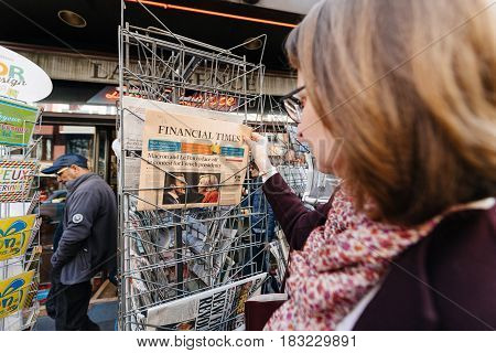 PARIS FRANCE - APRIL 24: Woman buy looks at press kiosk at UK newspaper Financial Times with pictures of French Presidential election candidates Emmanuel Macron Marine Le Pen a day after first round of French Presidential election on April 23 2017