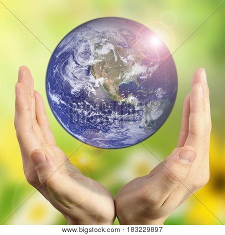 Hands holding the planet on blurred green bokeh background color of a natural tree with leaves, facing the sun-flared: the preservation of peace bio, CSR, environment concept: elements of this image furnished by NASA