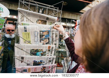 PARIS FRANCE - APRIL 24: Woman buy looks at press kiosk at Italian La Republica newspaper pictures of French Presidential election candidates Emmanuel Macron Marine Le Pen a day after first round of French Presidential election on April 23 2017