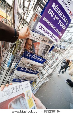 PARIS FRANCE - APRIL 24: Man buy looks at press kiosk at French newspaper Les Echos with pictures of French Presidential election candidates Emmanuel Macron Marine Le Pen a day after first round of French Presidential election on April 23 2017