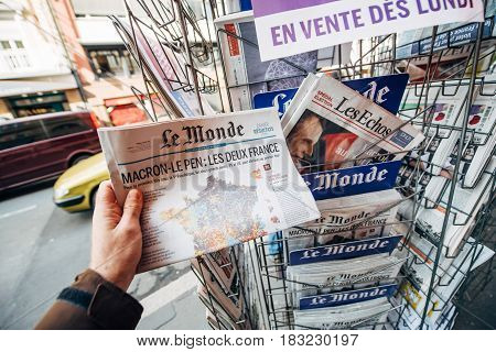PARIS FRANCE - APRIL 24: Man buy looks at press kiosk at French newspaper Le Monde with pictures of French Presidential election candidates Emmanuel Macron Marine Le Pen a day after first round of French Presidential election on April 23 2017