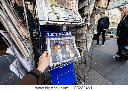 PARIS FRANCE - APRIL 24: Man buy looks at press kiosk at French newspaper with pictures of French Presidential election candidates Emmanuel Macron Marine Le Pen a day after first round of French Presidential election on April 23 2017