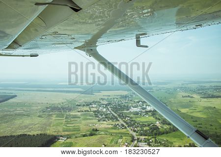 View to the rural lanscape and village from the board of a light plane