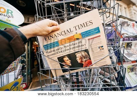 PARIS FRANCE - APRIL 24: Man buy looks at press kiosk at UK Financial Times newspaper with pictures of French Presidential election candidates Emmanuel Macron Marine Le Pen a day after first round of French Presidential election on April 23 2017