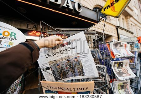 PARIS FRANCE - APRIL 24: Man buy looks at press kiosk at US The New York Times newspaper with pictures of soldiers vigipirate walking with Elections posters in the background - secure measures after attacks in PAris