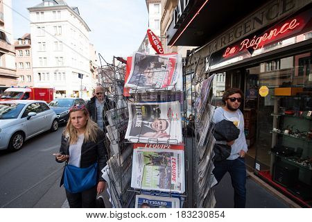 PARIS FRANCE - APRIL 24: WPedestrian walking newar press kiosk with International newspapers pictures of French Presidential election candidates Emmanuel Macron Marine Le Pen a day after first round of French Presidential election on April 23 2017
