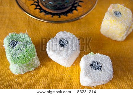 Turkish delight in a coconut crumb and cup of coffee