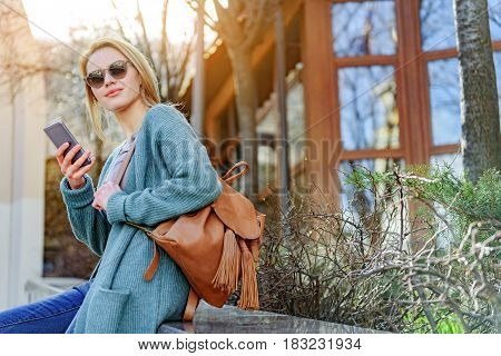 Confident young woman is sitting on bench outdoors with relaxation. She is using mobile phone and looking forward with pretty smile. Lady is holding bag