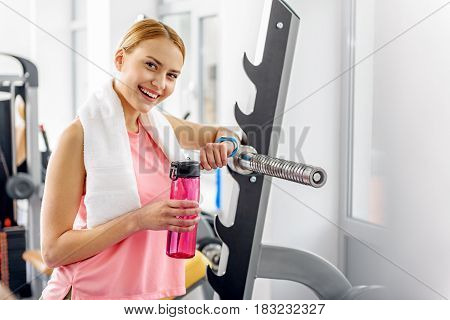 Portrait of half length female demonstrating cheeriness during train in fitness center . She drinking water