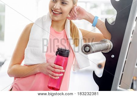 Woman expressing gaiety while leaning on exercise equipment in gym. She keeping blender bottle in hand