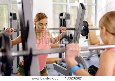 Young female expressing carefulness. She squatting with barbell in gym. She looking at her reflection in mirror